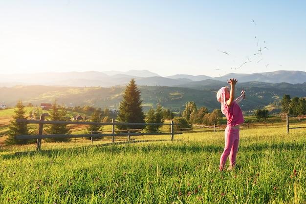 Bebê feliz pequeno bonito jogar ao ar livre no início da manhã no gramado e admirar a vista para as montanhas. copie o espaço para o seu texto