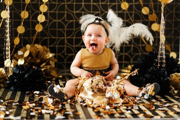 Bebê feliz que come o bolo em sua primeira festa de anos. cakesmash para menina