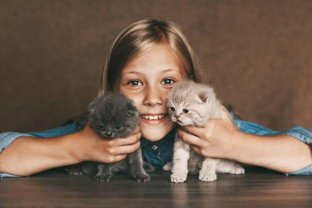 Bebê feliz, segurando lindos gatinhos britânicos