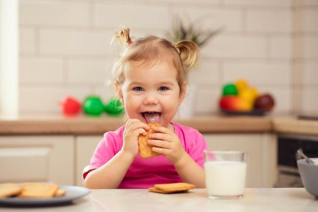 Bebê feliz sentado à mesa da cozinha e comendo com apetite