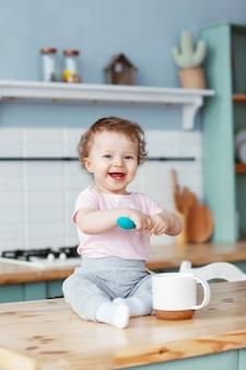 Bebê feliz sentado na cozinha em cima da mesa, segurando uma colher de plástico para comida nas mãos e sorrindo amplamente