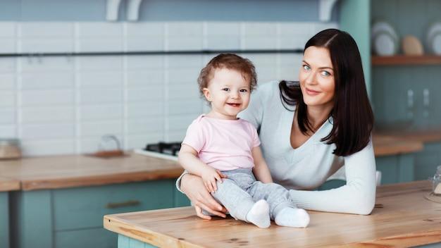 Bebê feliz sentado na mesa da cozinha com a mãe e sorrindo