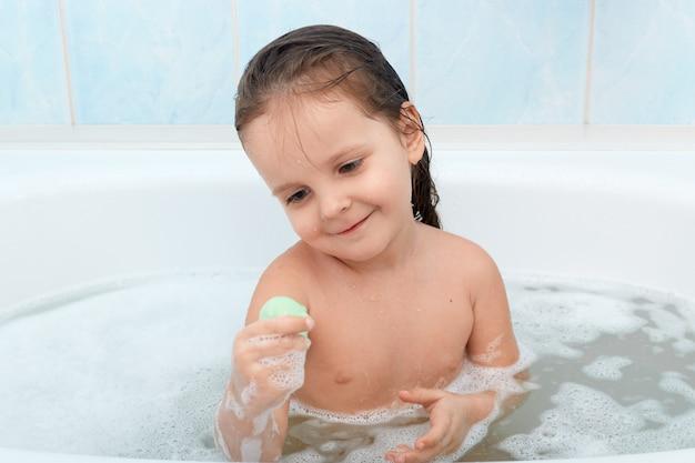 Bebê feliz tomando banho sozinho, brincando com bolhas de espuma e seu novo brinquedo.