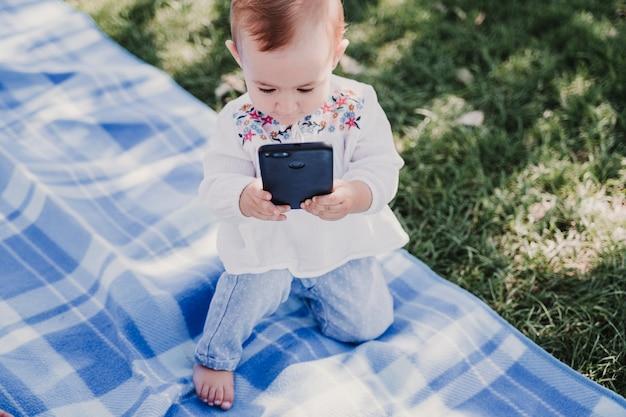 Bebê feliz usando telefone celular ao ar livre. conceito de tecnologia