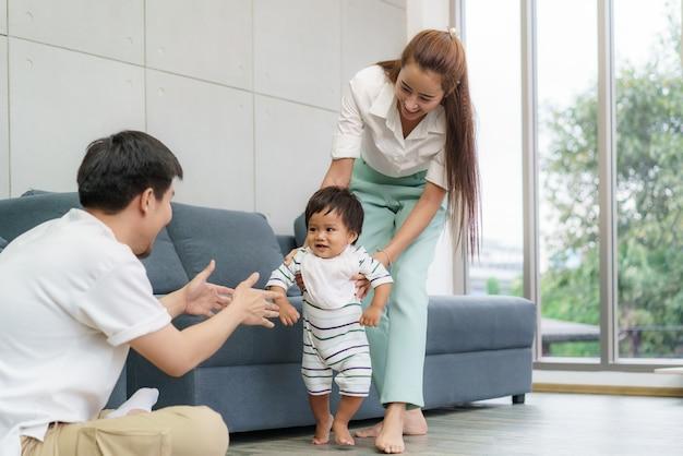 Bebê filho asiático dando os primeiros passos a pé em frente a seu pai. bebezinho feliz aprendendo a andar com a ajuda da mãe e ensinando como andar suavemente em casa