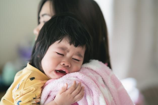 Bebê fofo asiático chorando nas mãos da mãe