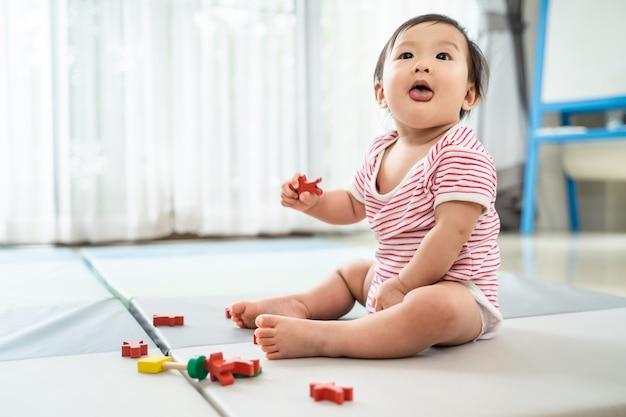 Bebê fofo asiático sentado e jogando um brinquedo pequeno na esteira macia em casa.