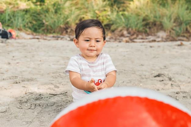 Bebê fofo brincando com bola na praia