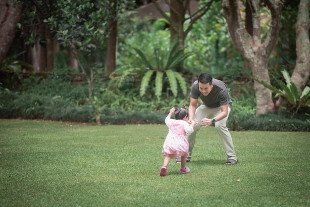 Bebê fofo brincando com o pai no jardim