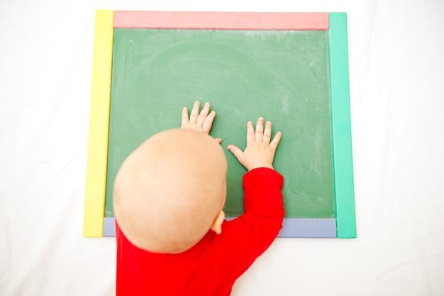 Bebê fofo brincando com o quadro-negro. conceito de desenvolvimento e treinamento