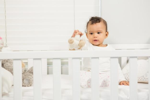 Bebê fofo brincando com pelúcia no berço