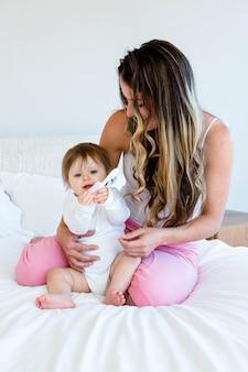 Bebê fofo brincando com um pente, sentado em uma cama com uma mulher morena