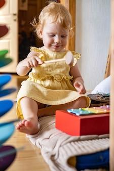 Bebê fofo brincando de xilofone infantil de madeira, brinquedos ecológicos, materiais de maria montessori