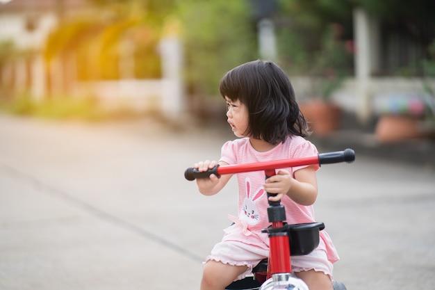 Bebê fofo chorando e andando de bicicleta