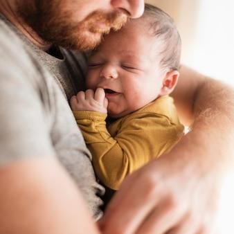 Bebê fofo close-up, sendo abraçado pelo pai