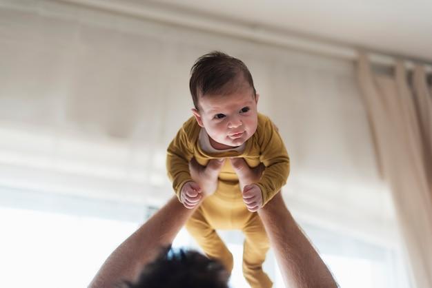 Bebê fofo close-up, sendo sustentado pelo pai