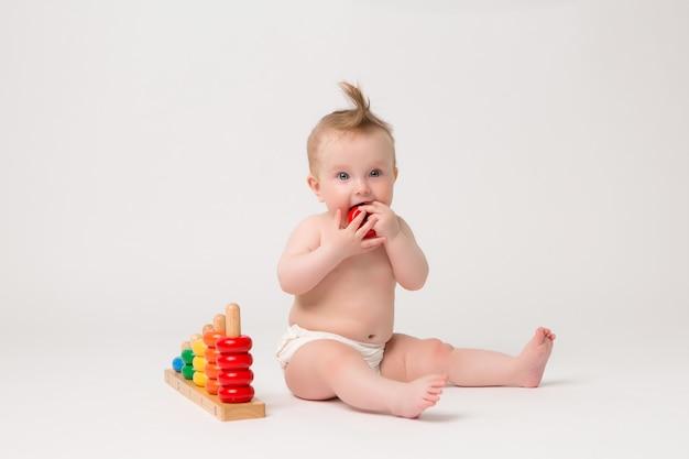 Bebê fofo com brinquedo de desenvolvimento em um fundo branco