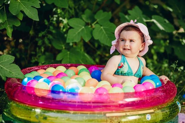 Bebê fofo com chapéu criativo chorando em sua piscina cheia de bolas coloridas
