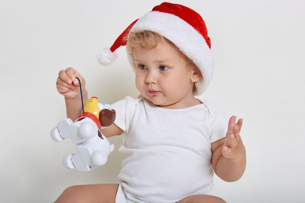Bebê fofo com chapéu de natal e macacão brincando com cachorro de plástico, criança encantadora segurando seu brinquedo, criança olhando para longe