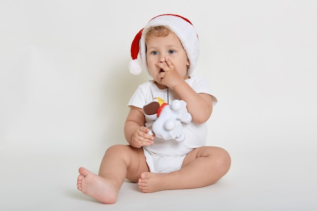 Bebê fofo com chapéu de papai noel brincando com cachorro de plástico contra uma parede branca