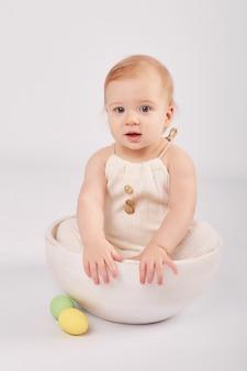 Bebê fofo com ovos de páscoa pintados
