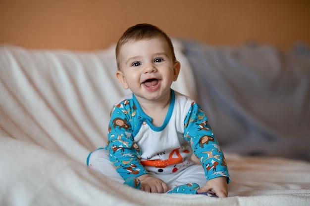 Bebê fofo com roupas azuis, deitado no sofá e sorrindo