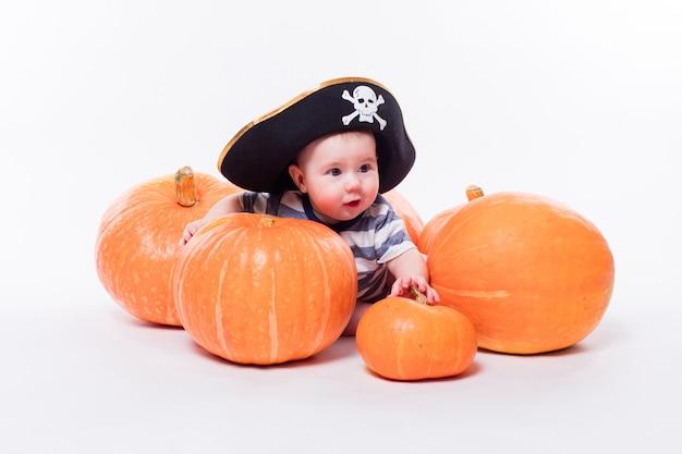 Bebê fofo com um chapéu de pirata na cabeça, deitado de bruços