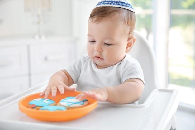 Bebê fofo comendo biscoitos festivos enquanto está sentado na cadeira alta