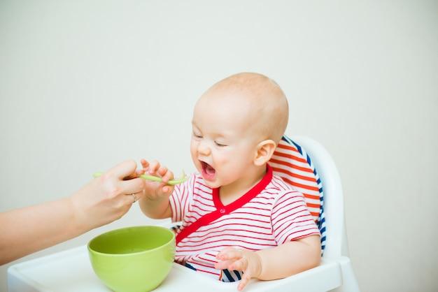 Bebê fofo comendo com colher sentado na cadeira alta
