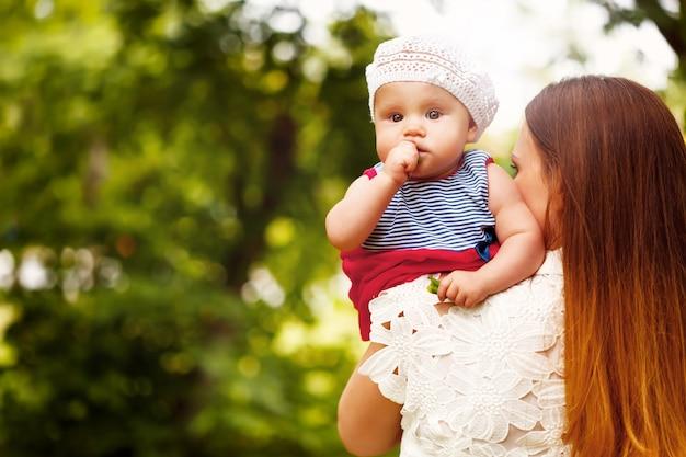Bebê fofo da criança sentada nas mãos da mãe