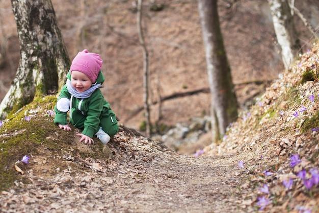 Bebê fofo da criança usando chapéu verde e macacão rosa na floresta de primavera cheia de íris selvagens.