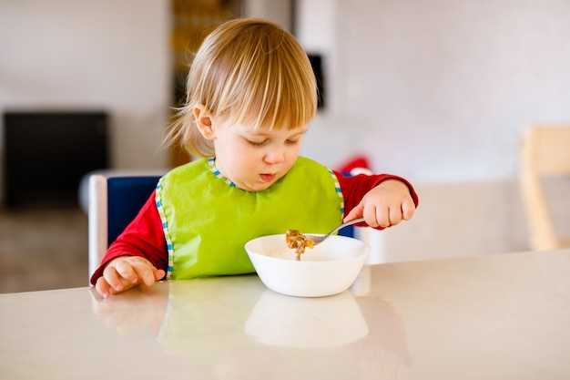Bebê fofo de 1,4 anos, sentado na cadeira alta para crianças e comendo vegetais sozinho na cozinha branca.