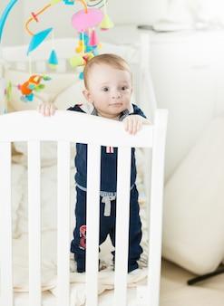 Bebé fofo de 9 meses de pé no berço