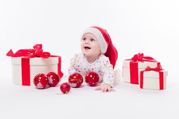 Bebê fofo deitado de bruços em um boné de ano novo entre o natal