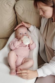 Bebê fofo deitado em uma pequena cama branca macia e tomando leite