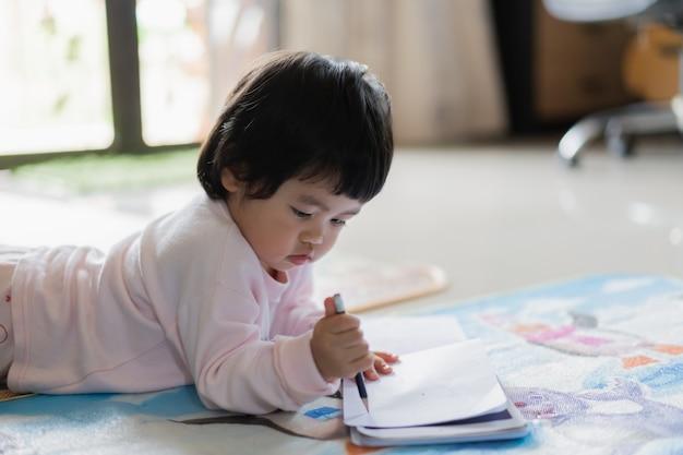 Bebê fofo desenhando no caderno no chão