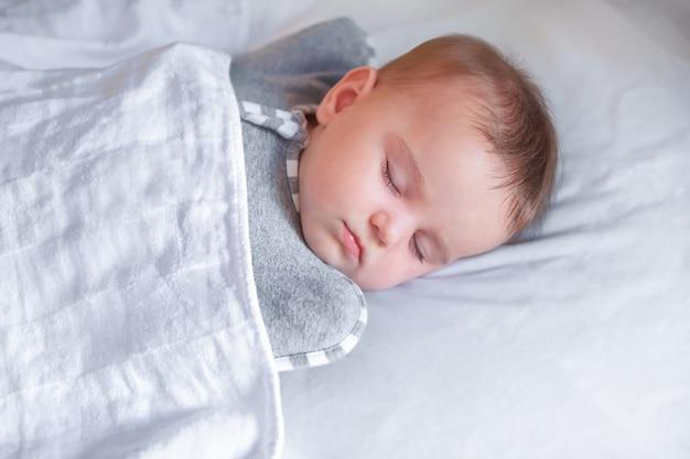 Bebê fofo dorme no berço. a criança dorme docemente em um lençol branco