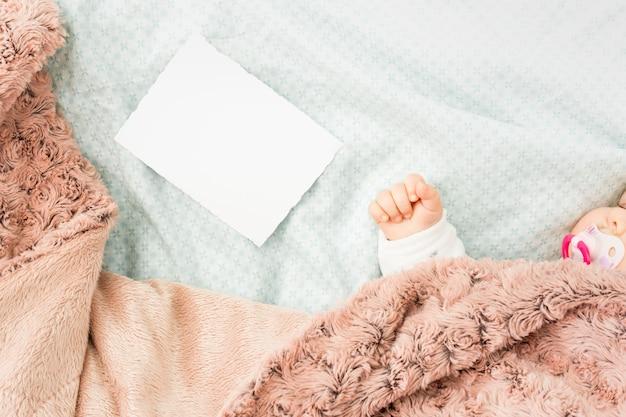 Bebê fofo dormindo na cama perto de papel em branco
