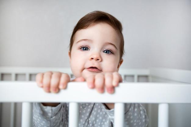 Bebê fofo e curioso em pé em uma cama de berço branco.