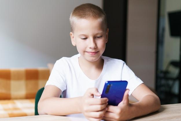 Bebê fofo e feliz filho sentado à mesa, relaxando e se divertindo com o celular, jogando jogos assistindo