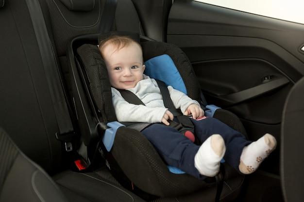 Bebê fofo e sorridente sentado na cadeirinha do carro