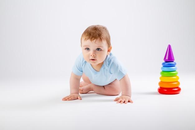 Bebê fofo em body azul brinca com pirâmide multicolorida