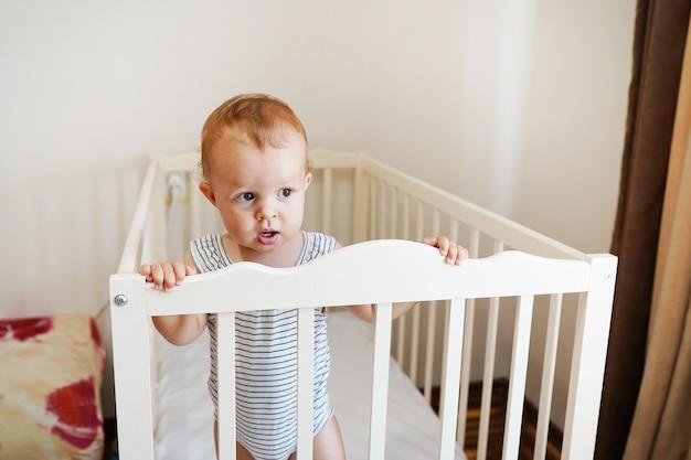 Bebê fofo em pé em uma cama redonda branca. berçário branco para crianças. menina aprendendo a ficar no berço.