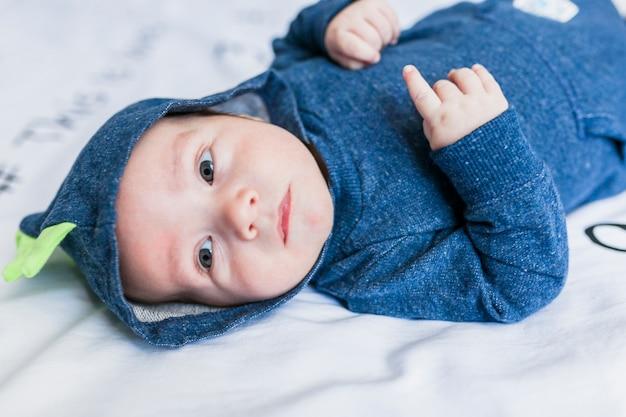 Bebê fofo em pijama de dinossauro