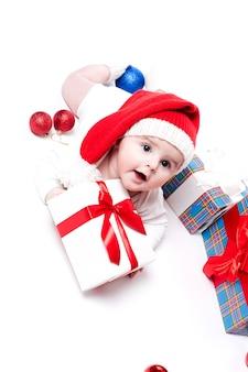 Bebê fofo em um boné vermelho de ano novo com um sorriso no rosto deitado