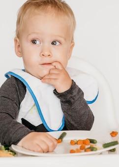 Bebê fofo em uma cadeira alta comendo sozinho