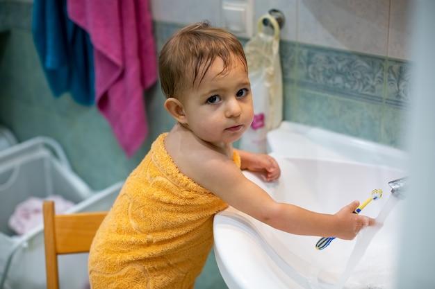 Bebê fofo em uma cadeira no banheiro enrolado em uma toalha lava uma escova de dentes na pia debaixo da torneira