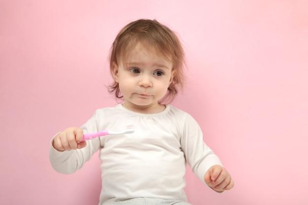 Bebê fofo menina escovando os dentes. vista do topo