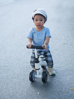 Bebê fofo menino asiático com capacete de segurança e protetor de cabeça aprendendo a andar com sua primeira bicicleta de corrida branca na estrada