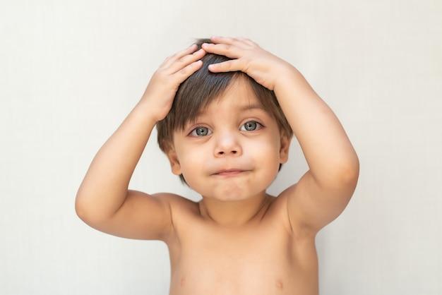 Bebê fofo menino criança - as mãos na cabeça